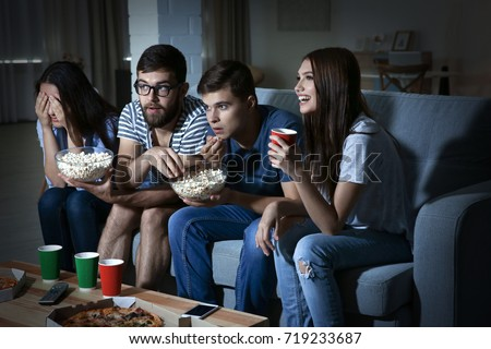 Friends watching TV in evening at home