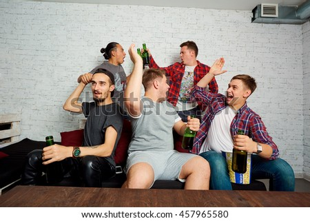 Friends watching TV together students with interest and emotion, drink beer, to the output. Friends fans rooting for their team. - stock photo