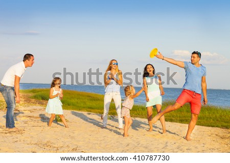 Friends with children playing with frisbee on the beach. Summer holiday and family concept