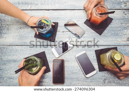 friends with cocktails. Four hands holding cocktails. Smart phones are down on the table. taking a break from technology and enjoying life - stock photo