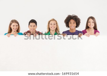 Friends with copy space. Cheerful young multi-ethnic people holding copy space and smiling at camera while isolated on white - stock photo
