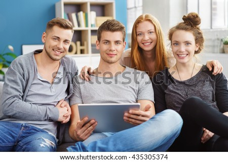 Friends with laptop computer seated on couch smile at camera in living room with blue painted walls as sun pours in through windows - stock photo