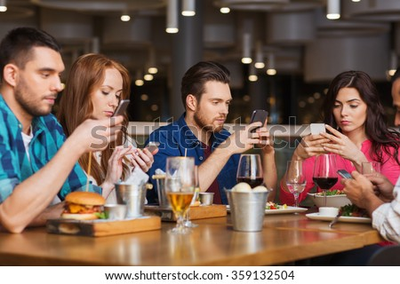 friends with smartphones dining at restaurant - stock photo