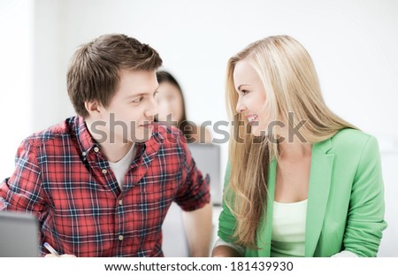 friendship and education concept - picture of smiling students looking at each other at school - stock photo