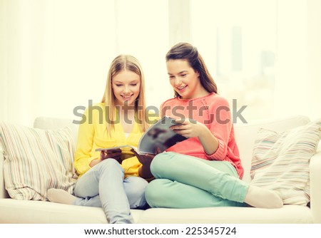 friendship and happiness concept - two girlfriends reading magazine at home - stock photo