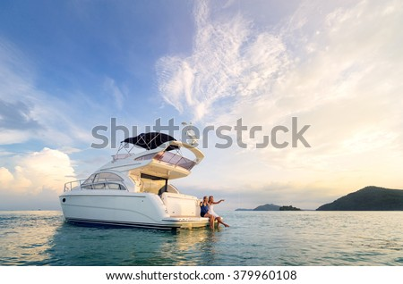 Friendship and luxury vacation. Two happy young women sitting on the yacht deck looking and pointing away sailing the sea. - stock photo