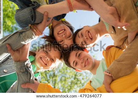 friendship and people concept - group of happy teenage friends holding hands outdoors