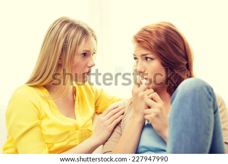 friendship and people concept - one teenage girl comforting another after break up - stock photo