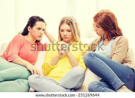 friendship and people concept - two teenage girls comforting another after break up - stock photo