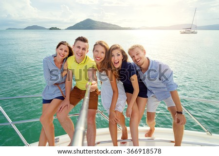 Friendship and vacation. Group of young handsome men and women taking selfie togetherr on the yacht sailing the sea. - stock photo