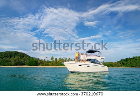 Friendship and vacation. Happy young people standing on the yacht deck and enjoying the view, sailing the sea. - stock photo
