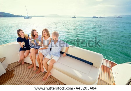Friendship and vacation. Party on the yacht. Group of laughing young people sitting on the deck drinking champagne sailing the sea. - stock photo