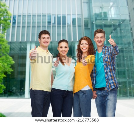 friendship, business, education and people concept - group of smiling teenagers showing thumbs up over campus background - stock photo