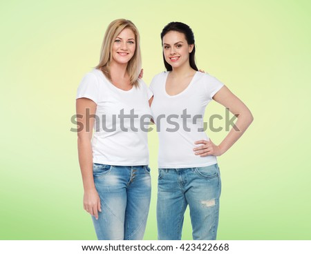 friendship, diverse, body positive and people concept - group of happy different women in white t-shirts hugging over green natural background