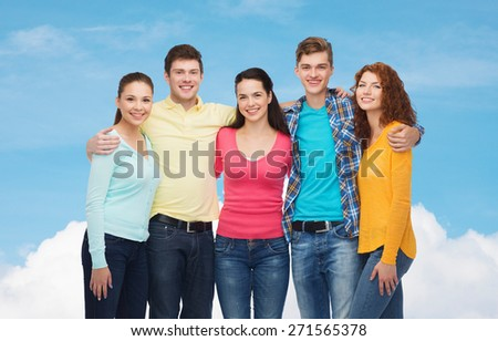 friendship, dream and people concept - group of smiling teenagers standing and hugging over blue sky with white cloud background - stock photo