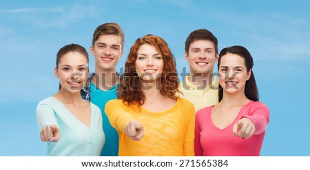 friendship, dream, future and people concept - group of smiling teenagers pointing fingers on you over blue sky with white cloud background