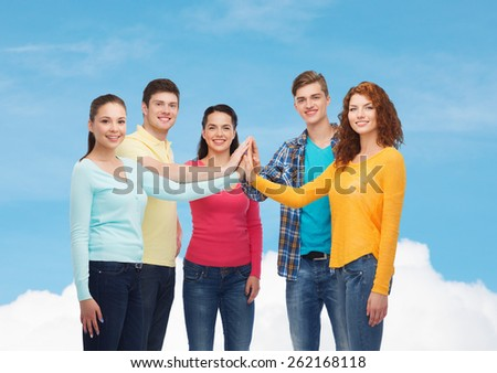 friendship, dream, teamwork, gesture and people concept - group of smiling teenagers making high five over blue sky with white cloud background - stock photo