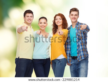 friendship, ecology, gesture and people concept - group of smiling teenagers pointing finger on you over green background - stock photo