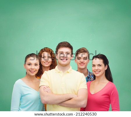 friendship, education, school and people concept - group of smiling teenagers standing over green board background