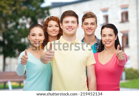 friendship, education, summer vacation and people concept - group of smiling teenagers showing thumbs up over campus background - stock photo