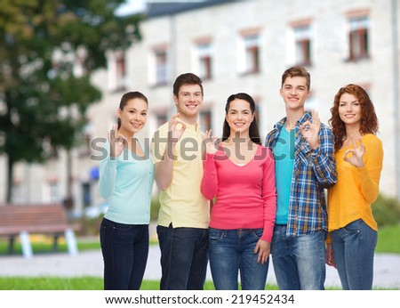 friendship, education, summer vacation and people concept - group of smiling teenagers showing ok sign over campus background - stock photo