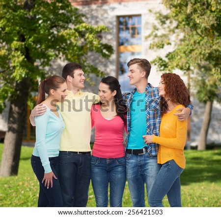 friendship, education, summer vacation and people concept - group of smiling teenagers standing and hugging over campus background