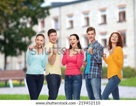 friendship, education, summer vacation, teamwork and people concept - group of smiling teenagers showing triumph gesture over campus background - stock photo