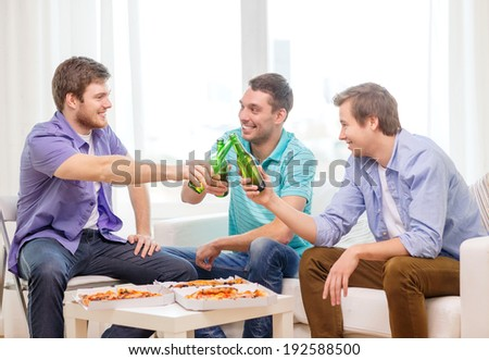 friendship, food and leisure concept - smiling male friends with beer and pizza hanging out at home - stock photo