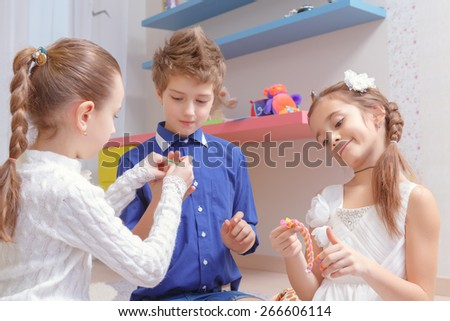 Friendship forever. Three school friends knitting rubber friendship bracelets together - stock photo