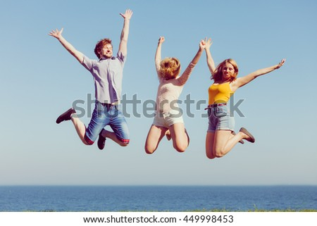 Friendship freedom summer holidays concept. Group of friends boy two girls jumping outdoor against sky