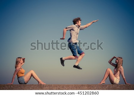 Friendship freedom summer holidays concept. Group of friends boy two girls spending time together guy  jumping against sky