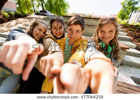 friendship, gesture and people concept - happy teenage friends or high school students pointing finger at you