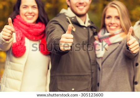 friendship, gesture, season and people concept - close up of happy friends showing thumbs up in autumn park - stock photo