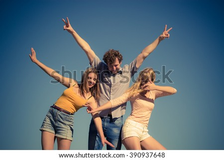 Friendship happiness summer holidays concept. Group of friends boy two girls having fun outdoor stretching arms celebrating, against sky