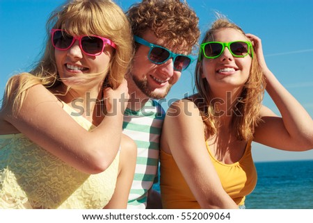 Friendship happiness summer holidays concept. Group of friends boy two girls in sunglasses having fun outdoor,  joy playful mood.