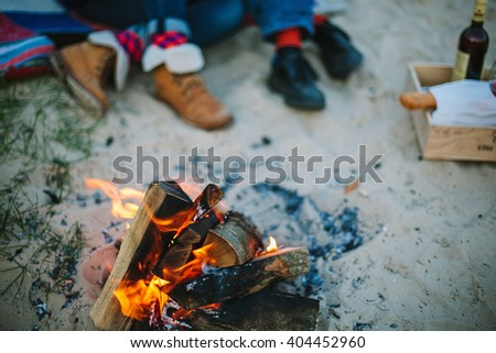 Friendship, happiness, summer vacation, holidays and people concept - Bonfire on beach and couple sitting on background out of focus. - stock photo