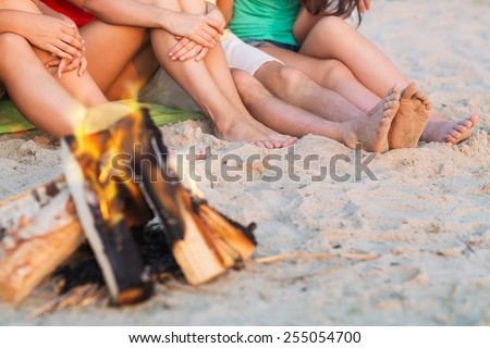 friendship, happiness, summer vacation, holidays and people concept - close up of friends sitting near fire on beach - stock photo