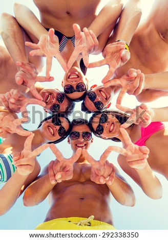 friendship, happiness, summer vacation, holidays and people concept - group of smiling friends wearing swimwear and showing victory or peace sign standing in circle over blue sky - stock photo