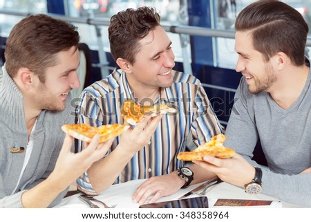 Friendship is forever. Cheerful male friends enjoying pizza together at the local restaurant - stock photo
