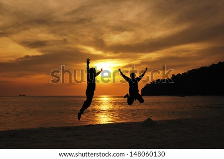 Friendship jumping in silhouette