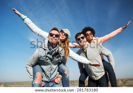 friendship, leisure and people concept - group of happy teenage friends in sunglasses having fun outdoors - stock photo