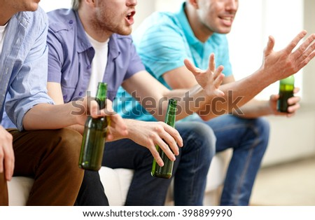 friendship, leisure, people and alcohol concept - close up of happy male friends drinking beer and watching tv at home - stock photo