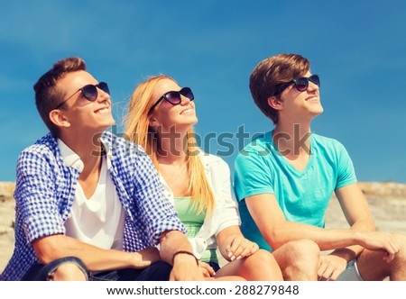 friendship, leisure, summer and people concept - group of smiling friends sitting on city street - stock photo