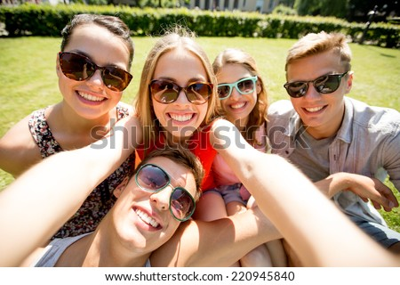 friendship, leisure, summer, technology and people concept - group of smiling friends making selfie with smartphone, camera or tablet pc in park - stock photo