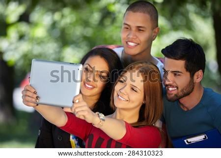 friendship, leisure, summer, technology and people concept - group of smiling friends making selfie with  tablet pc in park
