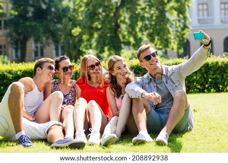 friendship, leisure, summer, technology and people concept - group of smiling friends with smartphone making selfie in park