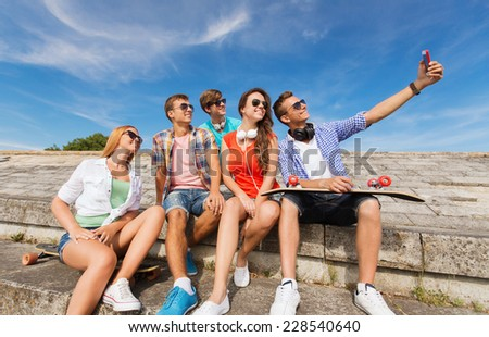 friendship, leisure, summer, technology and people concept - group of smiling friends with skateboard and smartphone making selfie outdoors - stock photo