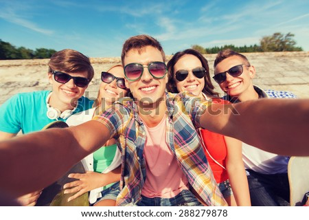 friendship, leisure, summer, technology and people concept - group of smiling friends with skateboard making selfie outdoors - stock photo