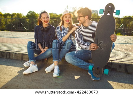 Friendship, leisure, summer, technology and people concept - smiling friends having fun outdoors