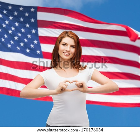 friendship, patriotic and happy people concept - smiling girl in white t-shirt showing heart with hands - stock photo